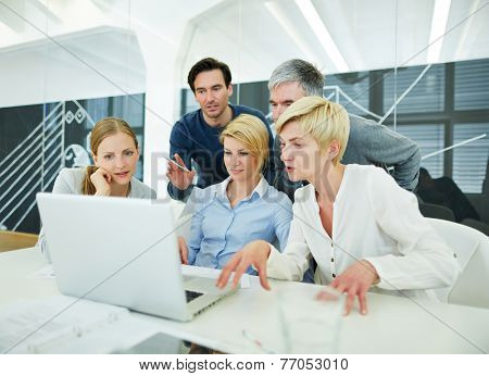 Business team in office looking at laptop computer monitor