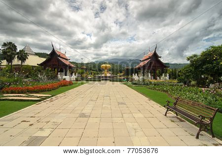 View To The Path With Few Benches Through The Garden Featuring Traditional Thai Temples, Flowers And