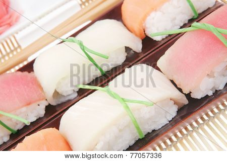 Japanese Cuisine - Set of Tuna (maguro) Salmon (sake) and Eel (unagi) Nigiri Sushi  with Wasabi and Ginger on bamboo mat isolated over white background