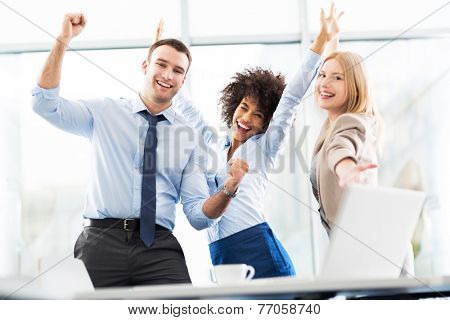 Business people cheering with arms raised