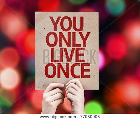 You Only Live Once written on colorful background with defocused lights
