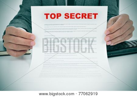 a man wearing a suit showing a document headed by the words top secret