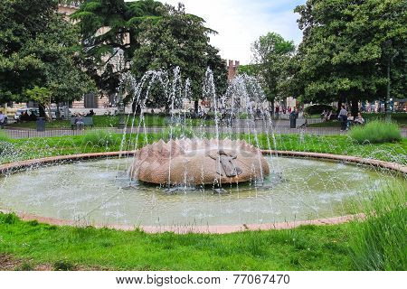 People Relax By The Fountain Alps In Square At Piazza Bra In Verona, Italy