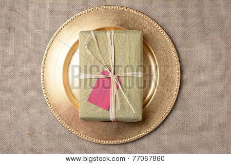 High angle shot of a tissue paper wrapped Christmas present on a gold charger on a burlap surface. The gift has a blank gift tag and is tied with raffia. Horizontal format.
