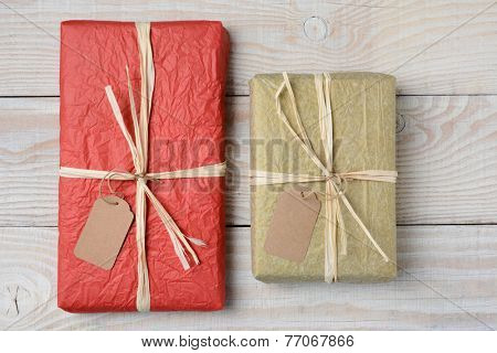 High angle shot of two presents on a white wood rustic table. Wrapped in crumpled tissue paper with blank gift tags. Horizontal format.
