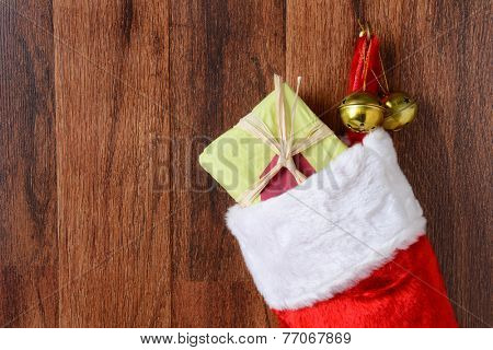 Closeup of a Christmas stocking filled with presents hanging from a hook on a wood wall. Two jingle bells hang from the hook also in vertical format.