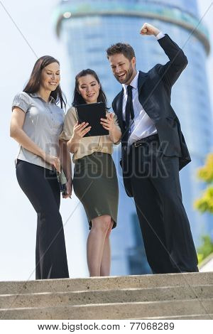Business team of successful man and women, businessman businesswoman, celebrating and using a tablet computer in a modern city