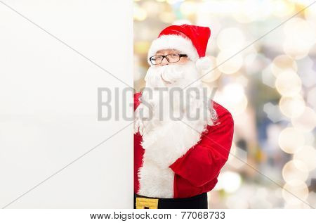 christmas, holidays, advertisement and people concept - man in costume of santa claus with white blank billboard making hush gesture over lights background