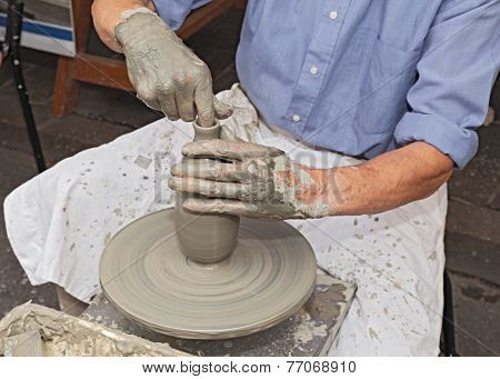 Potter Shaping Clay On A Potter's Wheel
