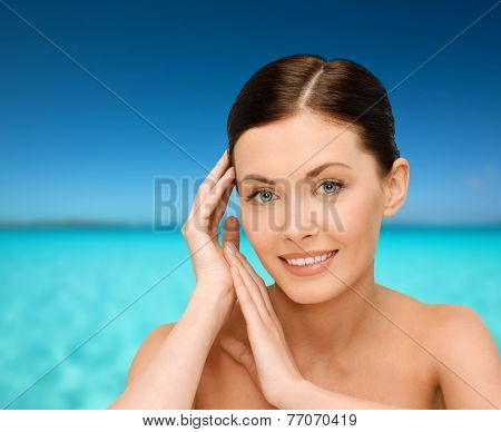 beauty, people and health concept - smiling young woman with bare shoulders over blue sky and sea background