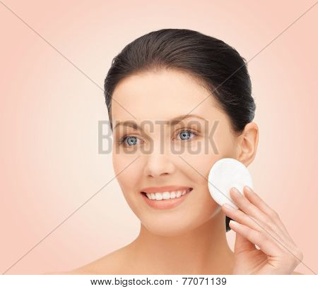 beauty, people and health concept - beautiful smiling woman cleaning face skin with cotton pad over pink background