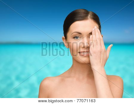 beauty, people and health concept - smiling young woman covering half of face with hand over blue sky and sea background