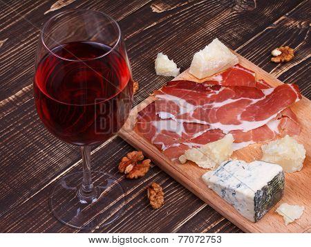 Glass of wine, cheese and on wooden background