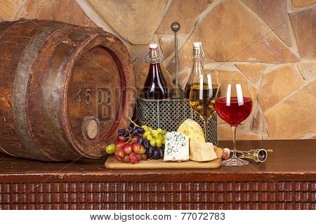 Wine cheese grapes and old wooden barrel with iron rings; still life