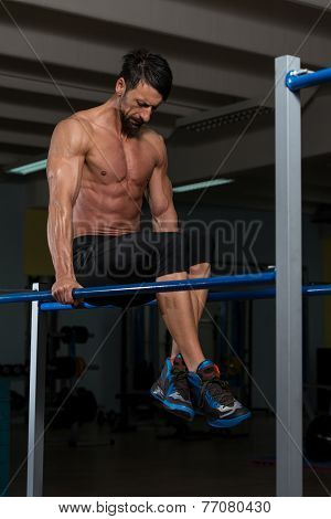 Athlete Doing Heavy Weight Exercise On Parallel Bars