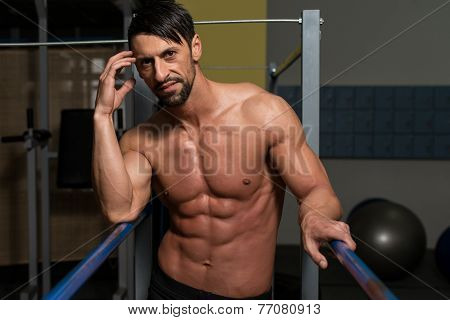 Bodybuilder Resting After Exercising On Parallel Bars