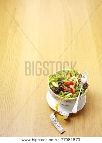 A bowl of mixed salad with a tape measure for healthy eating on a wooden background.