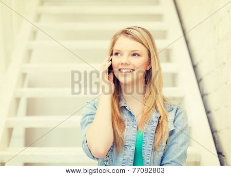 education and technology concept - smiling female student with smartphone sitting on staircase