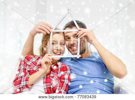 moving, real estate, relations and people concept - smiling couple with house shape made of measuring tape at new home