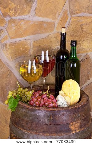 Glasses and bottles of wine cheese on old barrel with iron rings
