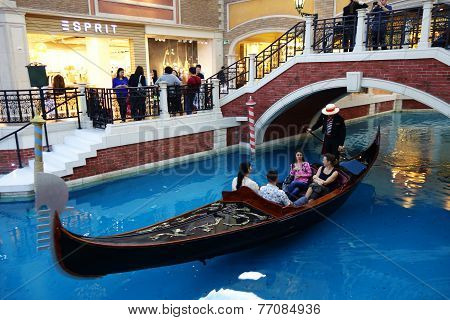Visitors Ride On Gondola Boat In Venetian Hotel In Macau
