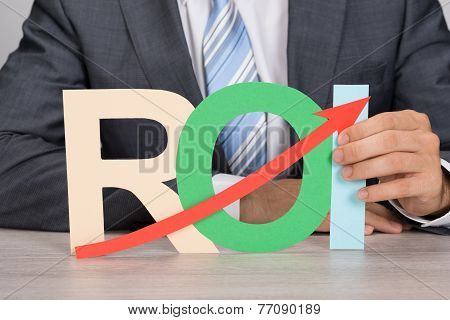 Businessman Holding Roi With Upward Moving Arrow