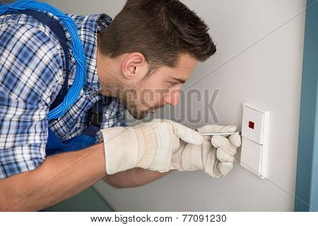 Man Repairing Light Switch At Home