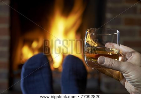 Man With Glass Of Whisky Relaxing By Fire