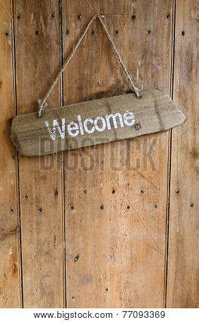 Welcome Sign Hanging From A Nail On An Old Rustic Wooden Oak Weathered Front Door.