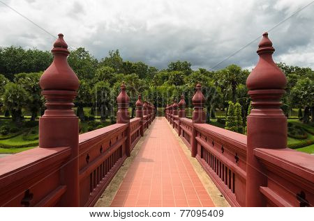 Bridge Paited In Red Leading To A Green Park With Palm Trees