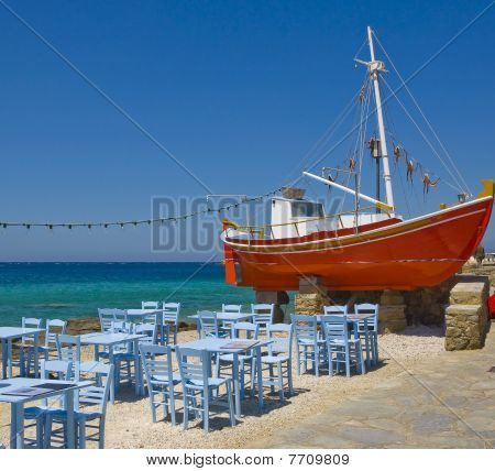 Tables In A Tavern Near The Sea And The Red Boat On  Mykonos