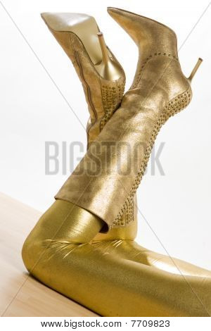 extravagant golden boots with leggins on light background