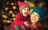 stock photo of christmas baby  - happy family mother and baby little daughter playing in the winter for the Christmas holidays - JPG