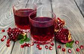 image of fruit-juice  - Two glasses of pomegranate juice with fresh fruits on wooden table - JPG