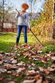 foto of spring-cleaning  - Caucasian farmer woman with a rake cleaning her garden of fallen leaves - JPG
