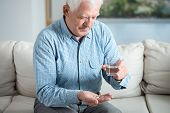 pic of older men  - Ill senior man taking pill and drinking water - JPG