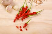image of scallion  - Red hot chilli peppers with a scallion and garlic on a wooden board - JPG