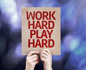picture of hard-on  - Work Hard Play Hard written on colorful background with defocused lights - JPG