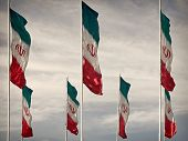 picture of iranian  - Rows of waving Iranian flags against cloudy blue sky edited with Vintage filter - JPG