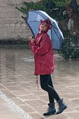pic of dancing rain  - Young woman dressed in red and walking in the rain with an umbrella - JPG