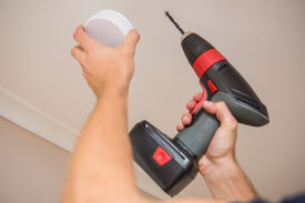 pic of smoke detector  - Handyman installing smoke detector with power tool on the ceiling - JPG
