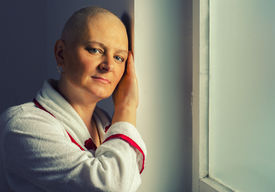 image of hospital gown  - Bald woman suffering from cancer standing in front of the hospital window - JPG