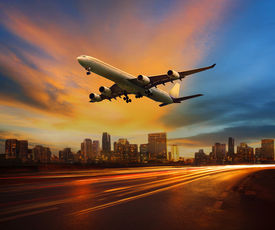 picture of urbanization  - beautiful lighting of vehicle in land transportation and passenger jet plane flying above urban scene use for transport business and people traveling theme