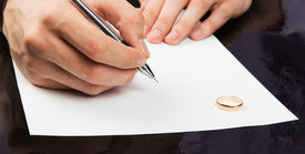 stock photo of divorce-papers  - Closeup of male hand signing divorce papers - JPG