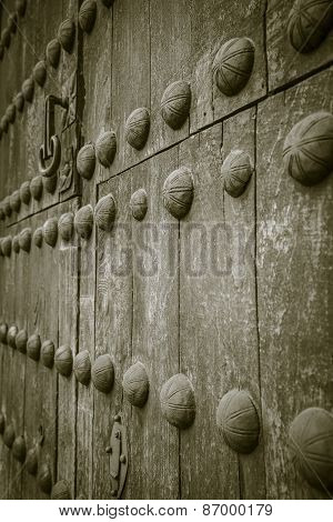 an ancient and brown wooden door with a knob