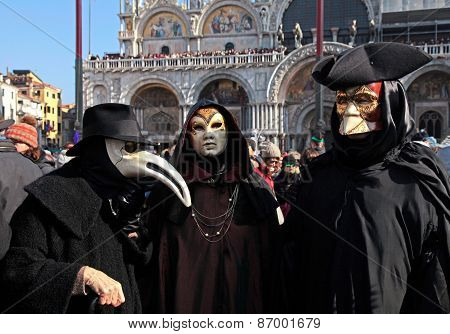 Masked Persons In Traditional Venetian Costume On San Marco Square, Venice