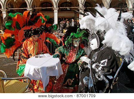 Masked Persons In Colorful Costume With Plumage Sitting In Cafe On San Marco Square, Venice