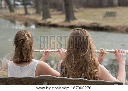 Girls playing flutes outside