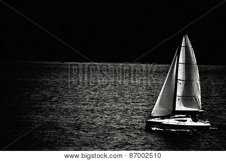 Journey on cruising and racing yacht under sail in the moonlight
