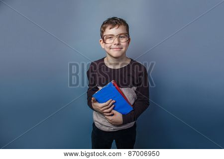 European-looking boy of ten years  in glasses reading  a book on